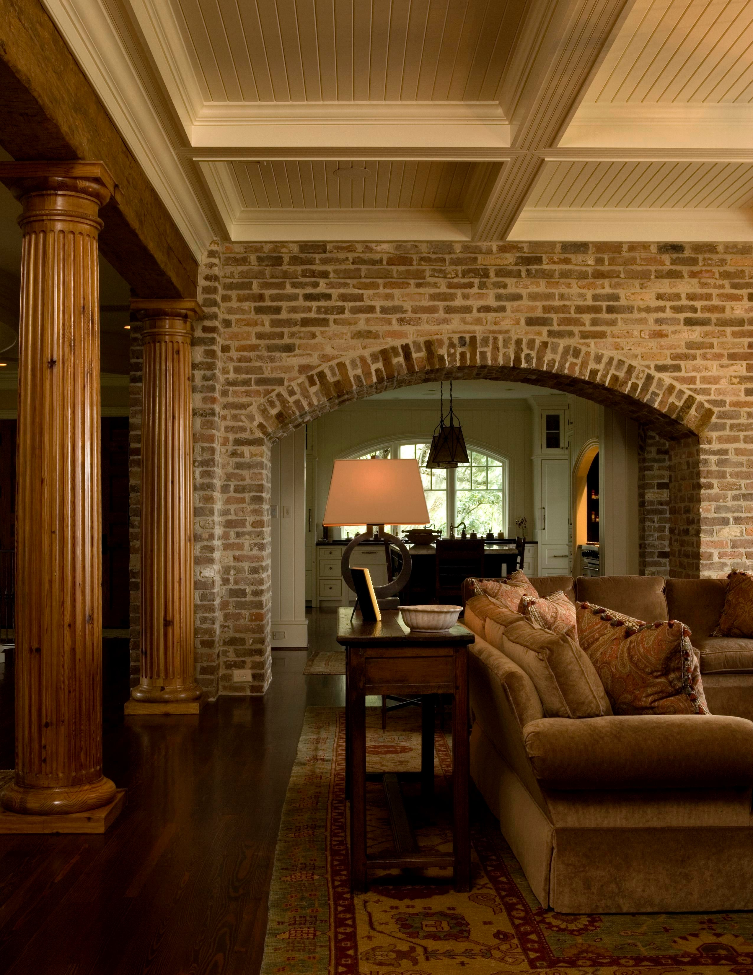 Living Room With Brick Arch, Natural Fluted Columns And Painted Wood Beams
