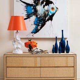 A large painting of a single tropical fish tops a raffia credenza.