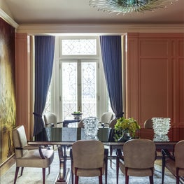 One focal point in this formal dining room is a green glass chandelier by Max Ingrand. The decorative panel, titled 'Ducks' is by Pierre Dunand for Jules Leleu.