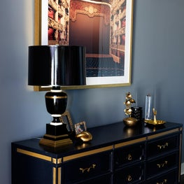 Black and gold console vignette against muted blue walls
