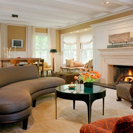 Living room in a Brookline period home with custom curved sofa designed by Tim Button