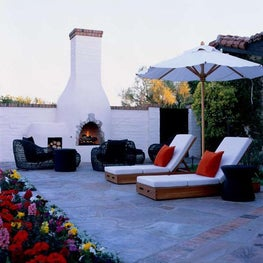 Two armless chaises resting poolside and gazing over a raised bed of flowers.