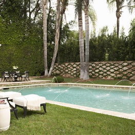 Beverly Hills pool with canopy and fountains, featuring Klismos furniture
