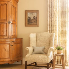 Living Room in a coastal home with antique pine corner cabinet and wing chair