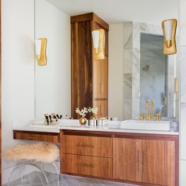 Modern family residence master bath with custom walnut cabinets and herringbone marble floors.