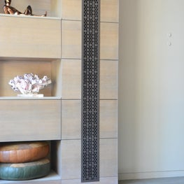 Metal heat register in Marshmallow pattern set in custom bookcase