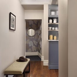 An over scaled printed grasscloth wall covering adds panache to a compact entry