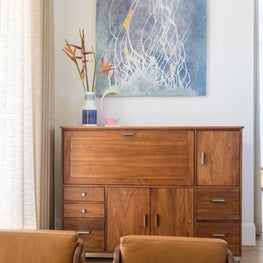 Finding Home a painting by Karrie Ross hangs above the dining cabinet. Dramatic hanging and upright Heleconia (psittacorum fire opal) bring life to the dining nook.