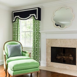 Neutral vignette is grounded on a dark wood floor with pops of green.