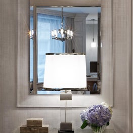 the lucite trimmed mirror refelcts a dramatic dining room fixture