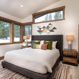 Bedroom furniture with bright colorful rug, bed pillows and art, floor mirror, hardwood floor and trim