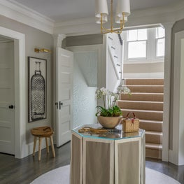 Neutral Foyer with Table Skirt, Wooden Stool and Brass Accents