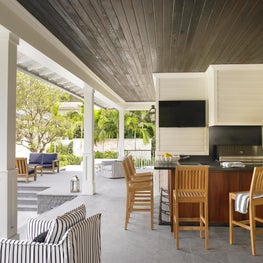 A casual-elegant looking patio is equipped with a full outdoor kitchen.