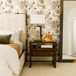 A warm modern bedroom with sepia toned wallpaper and cantilevered table lamps.