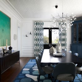 Dramatic Dining Room with pops of color in art and rug, branch chandelier