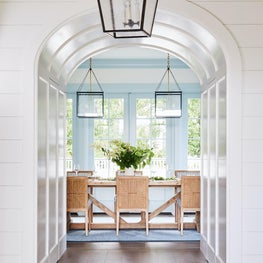 Blue and white dining room with painted trim and rattan chairs