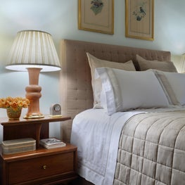 This bedroom features soft taupe & white bedding accented with a coral table lamp
