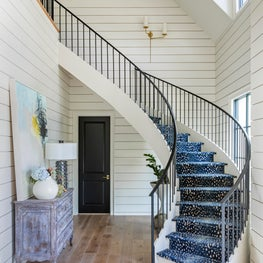 New Traditional Residence entry and staircase featuring Stark Antilocarpia stair runner, custom iron stair railing and clapboard walls.