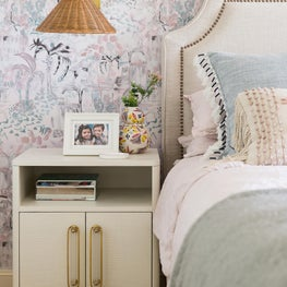 Master bedroom with abstract floral wallpaper, upholstered headboard with nailhead trim, and straw sconce