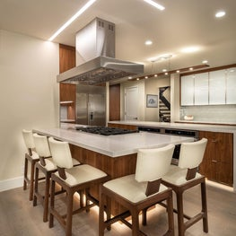 Open Plan Fusion - White kitchen with Iceberg leather counter stools and Carrara quartz countertop with a walnut base