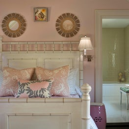 Feminine bed with pink garden stool, wall sconces and Asian-inspired florals