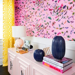 Home office vignette with bold, pink ground wallpaper with butterflies, pink buffet