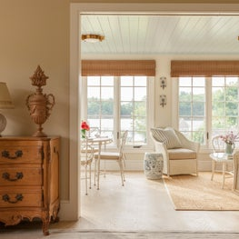 Sunroom in a coastal home is furnished with new and vintage wicker furniture.