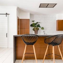 Minimalist kitchen bar seating with white floor tiles and blacksplash tiles