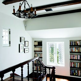 Stair hall with turned balusters, wood beams, built-in shelves, & rondel windows