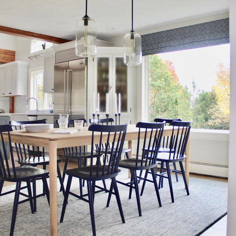 dining room/navy blue chairs/wooden table/glass pendants/roman shade/blue rug