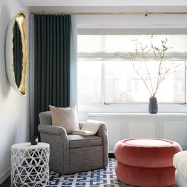 Upper East Side Living Room with green drapery, geometric rug & gold egg mirror