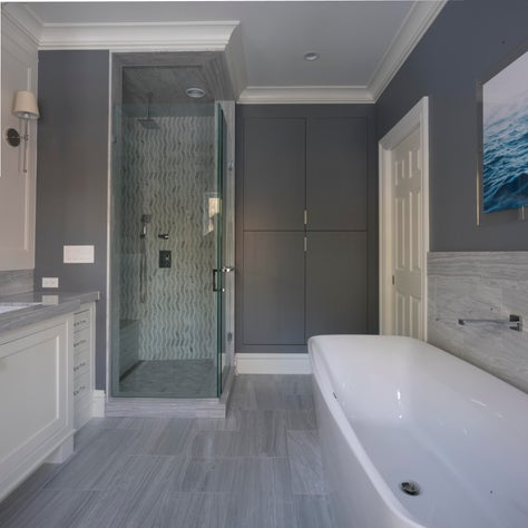 Gray walls, white fixtures and a green tiled shower create a relaxing ambiance.