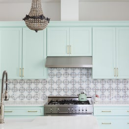 A Mint Green Kitchen with Brass Hardware and Moroccan Handmade Tiles