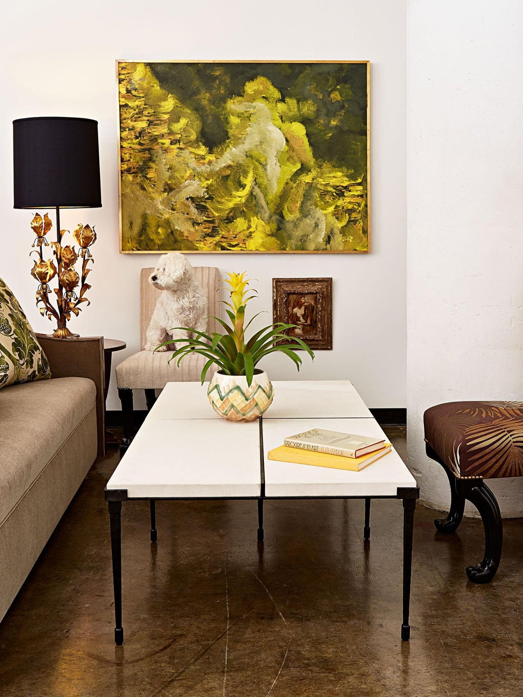 A loft's lounge is layered in tones of green and mustard against a crisp white backdrop and accented by many textures including gilt, marble, ceramic, velvet, concrete, and rich mahogany.