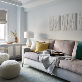 Upper East Side Family Room with stone relief art, furry chair and ombre throw