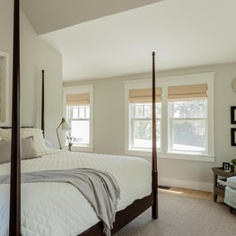 Dark mahogany 4-poster bed juxtaposed with an antique 24-light window