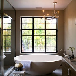 Large stone tub overlooks windows to the trees beyond.