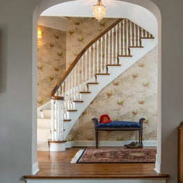 Foyer featuring curved staircase and delicate wallpaper