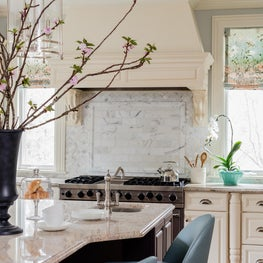 Transitional kitchen with carrara backsplash and blue leather counter stools
