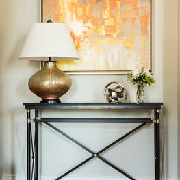 Commissioned art in bold oranges, yellows completes a table and lamp vignette.