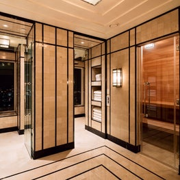 A streamlined sauna in hardwood is just beyond a glass door in the master bath.