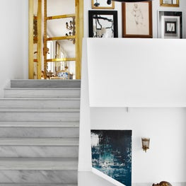 Clean lines in stairway with art collection and gold touches