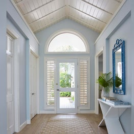 Tropical hallway with high paneled ceiling and arched window.