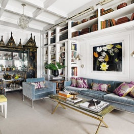 Eclectic library with streamlined midcentury furnishings and intricate linen press cabinet bar