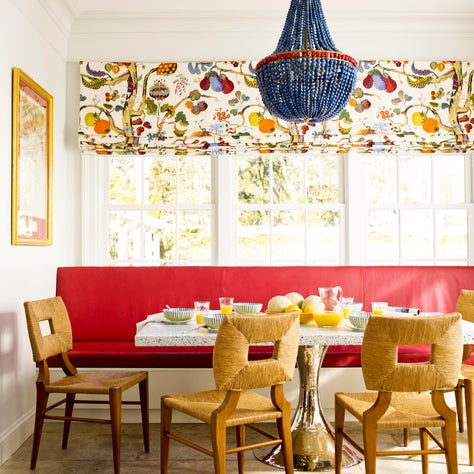 Bright breakfast nook with red banquette and blue chandelier