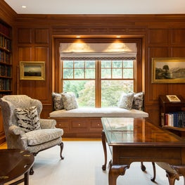 New Canaan, CT Paneled Library with Custom Window Seat, Roman Shade with Decorative Tape, Decorative Throw Pillows, Neutral Stark Carpet