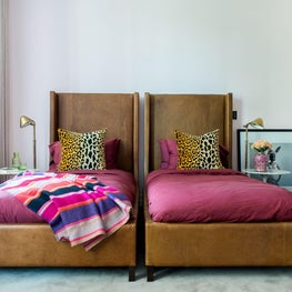 Kid's Bedroom with twin, leather beds, pink walls, and leopard pillows
