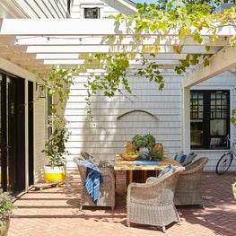 Dining on herringbone brick patio with grapevine trellis
