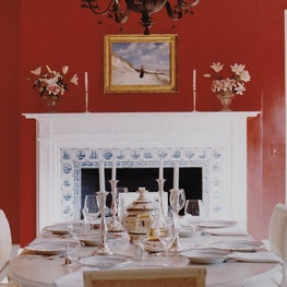 Red Dining Room with Antique Swedish Table and Delft Tile Fireplace