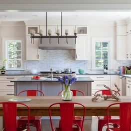 Bright red metal chairs and a wood table add character to neutral kitchen